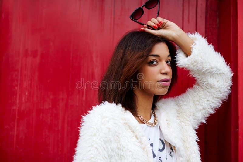 Attraktive schwarze weibliche Aufstellung auf dem roten Wandhintergrund, der Sonnenbrille in der Hand hält stockbilder