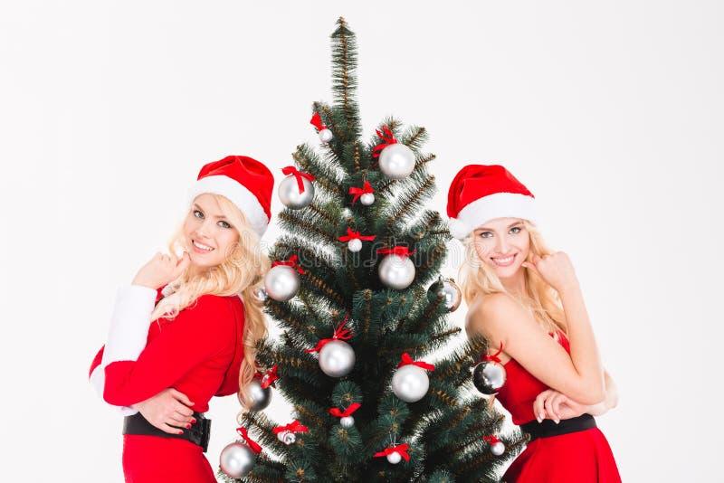 Attraktive Schwestern paart in roter Weihnachtsmann-Kleidung und -hüten lizenzfreie stockfotos