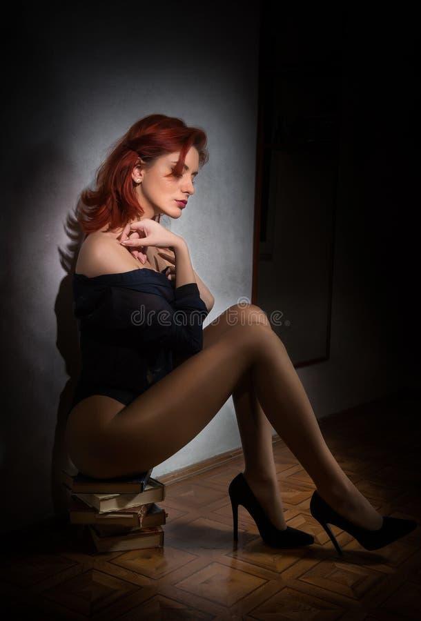 Attraktive sexy junge Frau im schwarzen Hemd und im Schlüpfer, die auf einem Stapel von Büchern auf dem Boden sitzt Sinnliche Rot lizenzfreies stockfoto