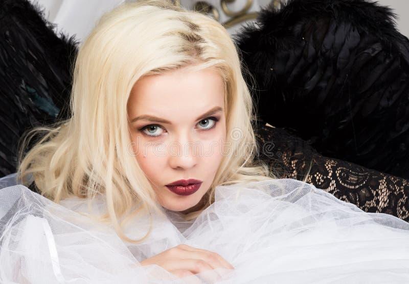 Attraktive sinnliche junge sexy Frau, die schwarze Wäsche und schwarzen die Flügel genießen auf einem Bett trägt stockfoto