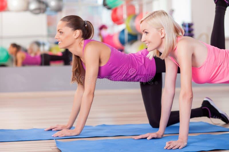 Attraktive Sitzmädchen tun Übungen in der Turnhalle lizenzfreie stockfotos