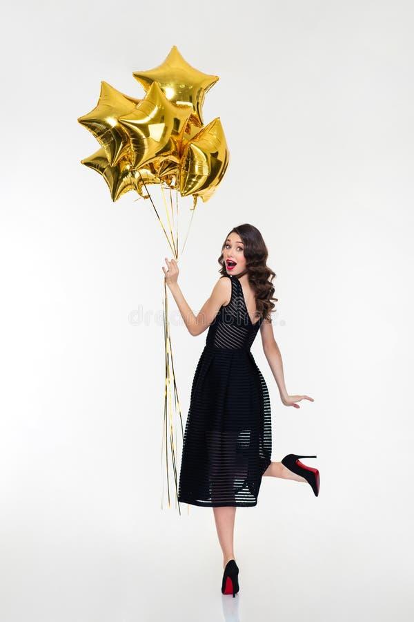 Attraktive spielerische glückliche Frau, die zurück schaut und goldene Ballone hält stockfotografie