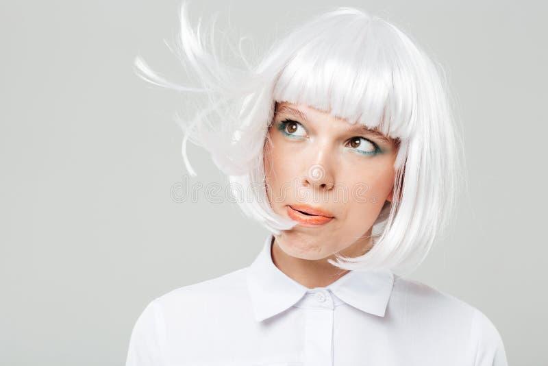 Attraktive spielerische junge Frau, die auf ihrem blonden Haar durchbrennt stockfotos