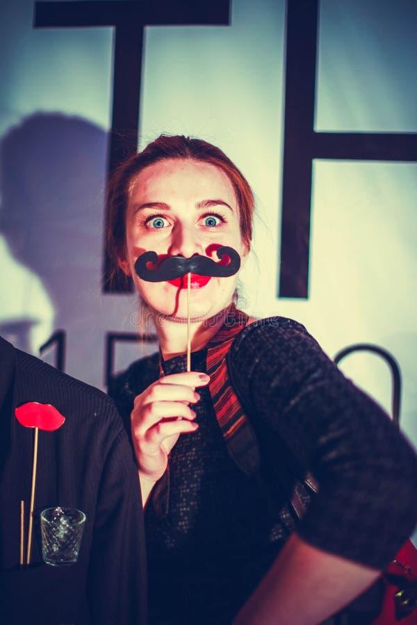 Attraktive spielerische schöne junge Frau, die Schnurrbart auf einem Stock hält lizenzfreie stockfotografie