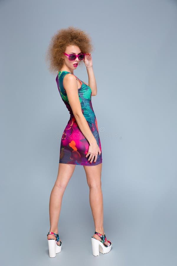 Attraktive spielerische weibliche Aufstellung im bunten Kleid lizenzfreie stockbilder