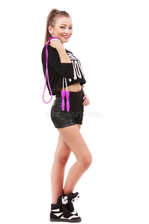 Attraktive sportliche Frau, die ein Springseil auf Weiß halten aufwirft stockbilder