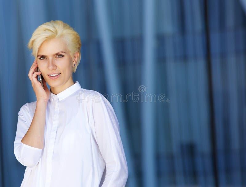 Attraktive Stadtfrau, die Handy verwendet stockfoto