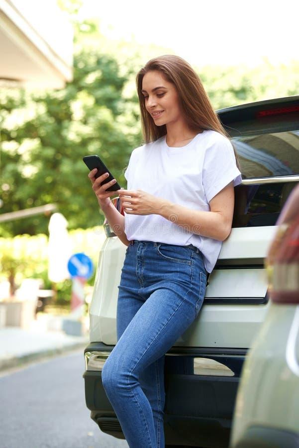 Attraktive Stellung der jungen Frau auf der Straße und den Versenden von SMS-Nachrichten stockfotos