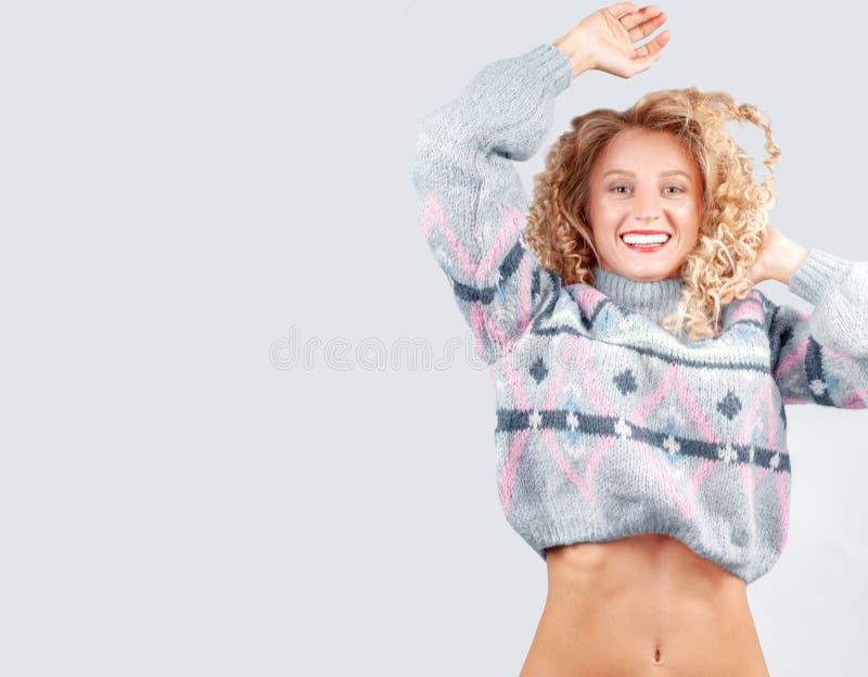 Attraktive Studentenfrau mit dem gelockten Haar gekleidet in der warmen Strickjacke stockfotografie