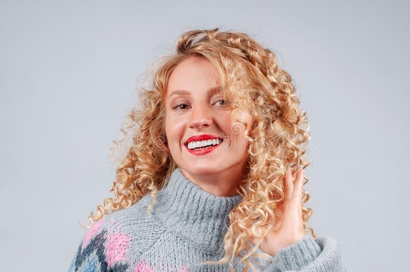 Attraktive Studentenfrau mit dem gelockten Haar gekleidet in der warmen Strickjacke lizenzfreies stockbild
