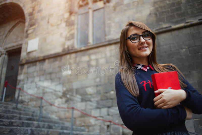 Attraktive Studentin in den Gläsern, die das rote helle Buch draußen steht halten lizenzfreie stockfotos