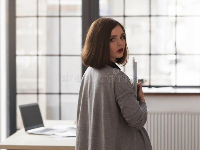 Attraktive Studentin, die in der halben Drehung steht lizenzfreie stockbilder