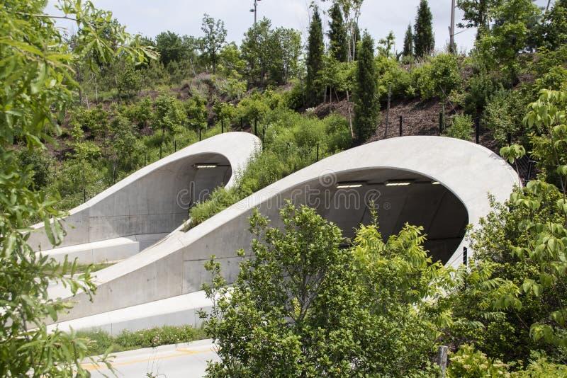Attraktive Tunnels ?ber Landstra?e in Tulsa Oklahoma nahe Park und Arkansas River mit vielen jungen B?umen gest?tzt, wie sie wach stockfotos
