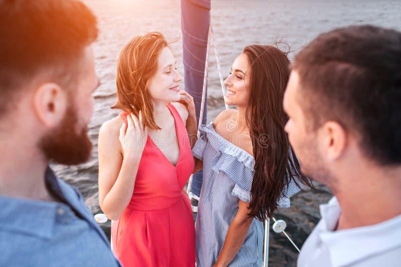Attraktive und erstaunliche Stände der jungen Frauen zusammen und einander betrachten Sie lächeln Männer stehen vor ihnen und lizenzfreies stockfoto