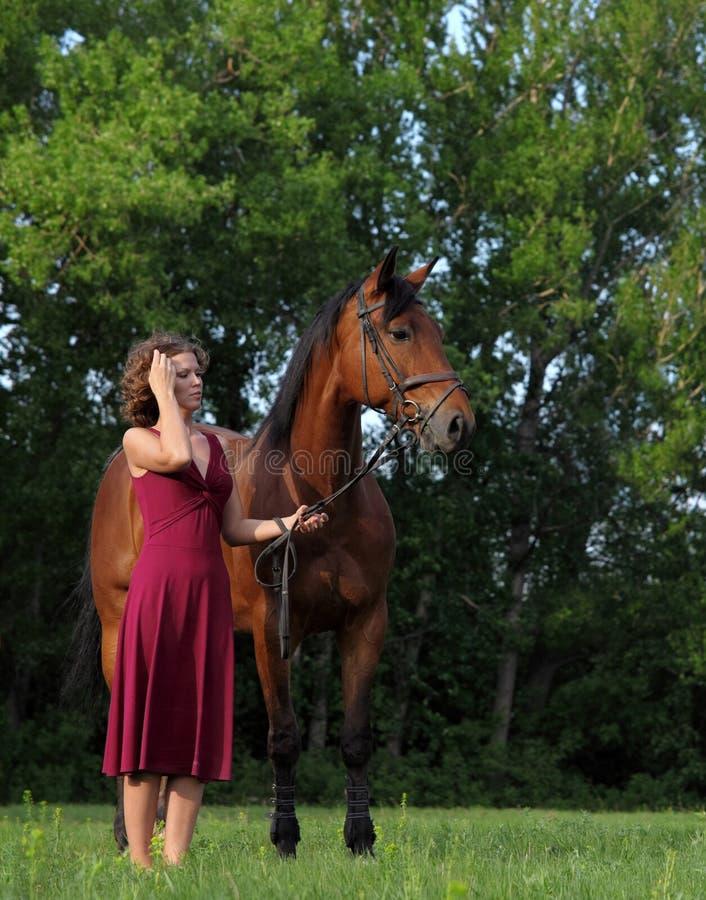 Attraktive und formschöne Rothaarigefrau mit Pferd stockfoto