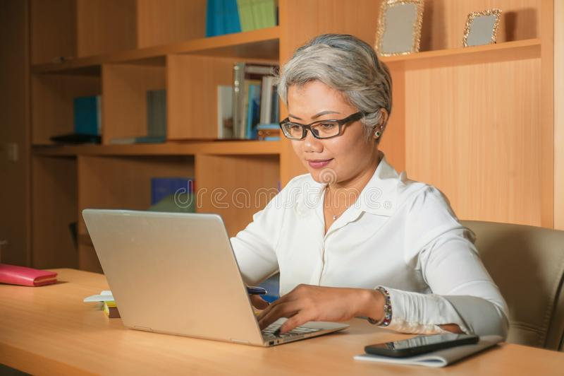 Attraktive und gl?ckliche erfolgreiche reife Asiatin, die entspannt am Laptopcomputertischl?cheln ?berzeugt im Gesch?ft arbeitet  lizenzfreie stockbilder