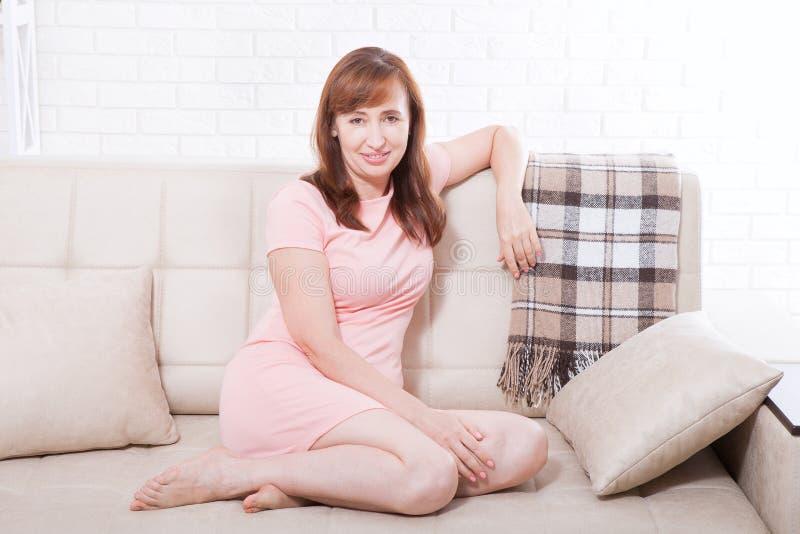 Attraktive und schöne mittlere Greisin, die auf Sofa sitzt und sich zu Hause entspannt wechseljahre stockfoto