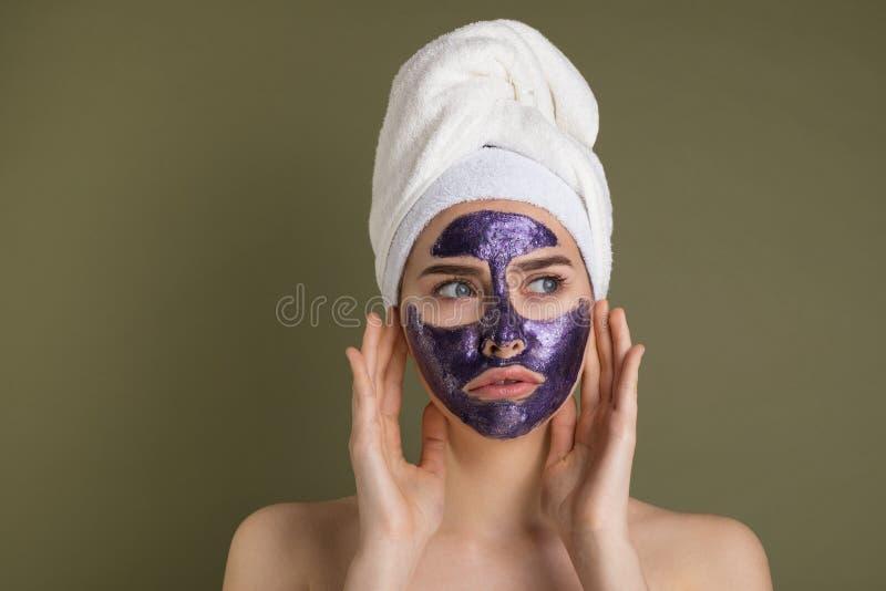 Attraktive unglückliche junge Frau mit purpurroter Gesichtsmaske und Duschtuch auf ihrem Kopf lizenzfreies stockfoto