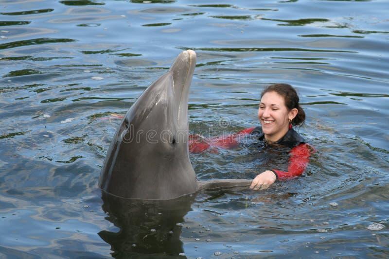 Attraktive weibliche Jugendlich-Schwimmen mit einem Delphin lizenzfreies stockbild