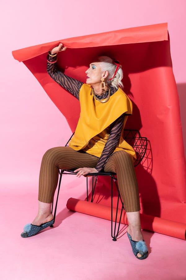 Attraktive weibliche Person, die über rotem Hintergrund sitzt stockbilder