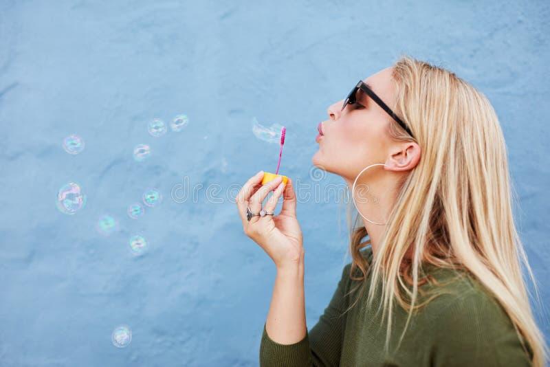 Attraktive weibliche Schlagseifenblasen stockbild