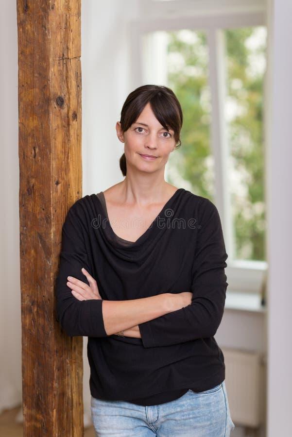 Attraktive zufällige Frau, die auf einer Wand sich lehnt stockbilder