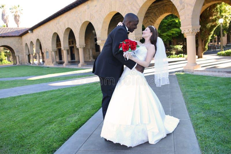 Attraktive zwischen verschiedenen Rassen Hochzeits-Paare an der Kirche lizenzfreies stockbild