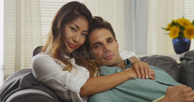 Attraktive zwischen verschiedenen Rassen Paare, die auf Couch sitzen lizenzfreie stockbilder