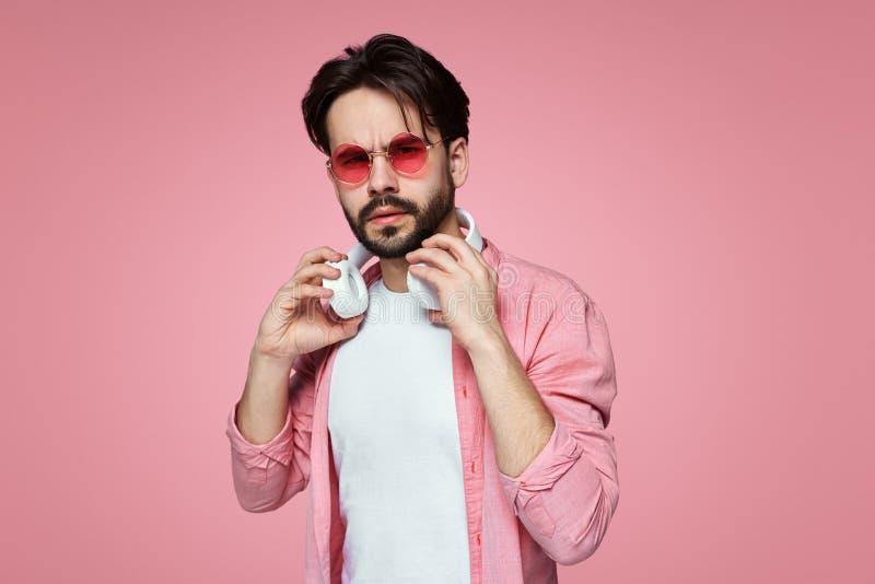 Attraktiver überzeugter handsine Mann, der der Kamera, tragender Kleidung und Sonnenbrille, weiße Kopfhörer des Halses an halten  lizenzfreie stockfotografie