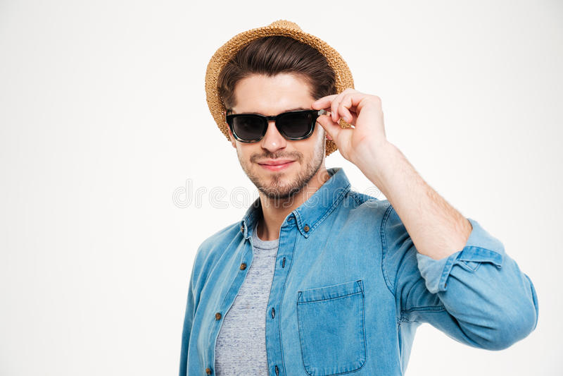 Attraktiver überzeugter tragender Hut und Sonnenbrille des jungen Mannes stockfotos