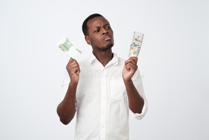 attraktiver afrikanischer Mann, der USA-Währung und Eurowährung welches entscheiden, um zu wählen hält Wie es besser, Geld zu spa lizenzfreie stockbilder