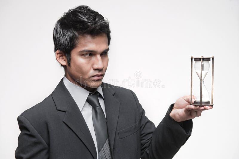 Attraktiver asiatischer Geschäftsmann, der eine Stunde Glas anhält stockbild
