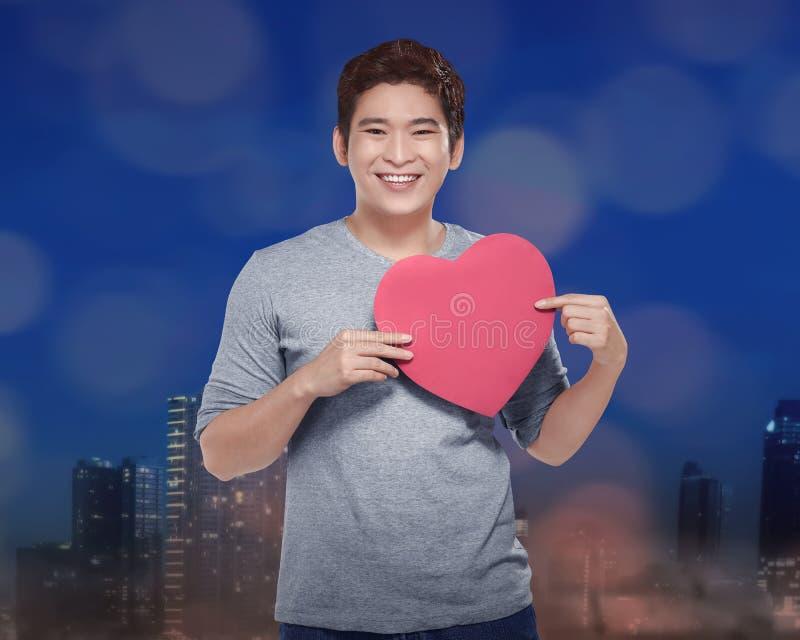 Attraktiver asiatischer Mann, der Herz in seiner Hand hält lizenzfreies stockfoto