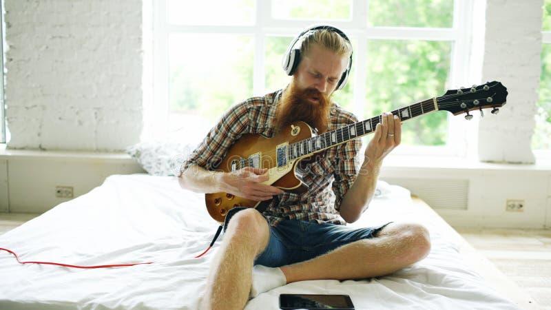 Attraktiver bärtiger Mann, der auf dem Bett lernt, Gitarre unter Verwendung des Tablet-Computers im modernen Schlafzimmer zu Haus lizenzfreie stockfotos