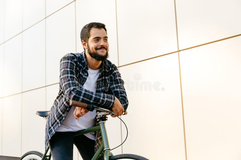 Attraktiver bärtiger Mann, der auf Fahrrad, draußen sitzt stockfoto