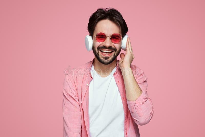 Attraktiver bärtiger Mann hört Lieblingslied, Gleichschläge in den Kopfhörern, angeschlossen an modernes zelluläres, lokalisiert  lizenzfreies stockfoto