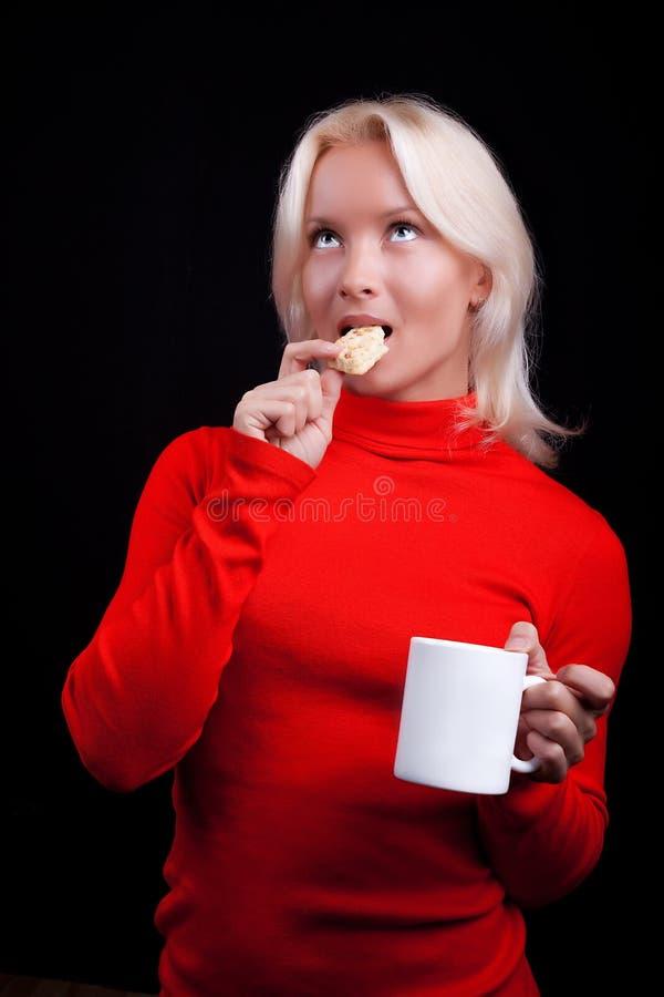 Attraktiver blonder trinkender Tee mit Plätzchen lizenzfreie stockbilder