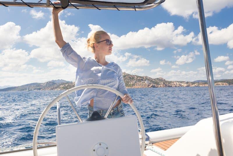 Attraktiver blonder weiblicher Kapitän, der das fantastische Katamaransegelboot am sonnigen Sommertag auf ruhigem blauem Meerwass stockbild
