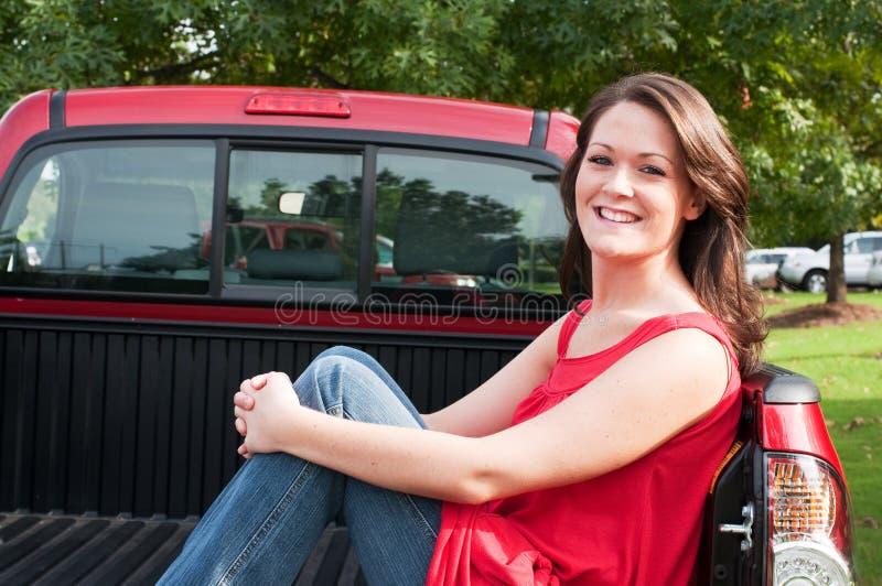 Attraktiver Brunette, der im Bett des Kleintransporters sitzt lizenzfreie stockfotos
