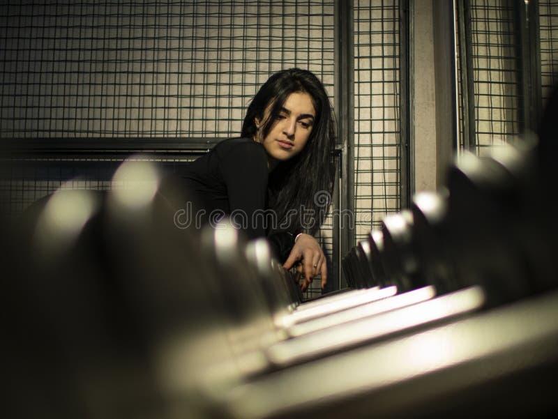 Attraktiver Brunette in einer schwarzen Spitze lehnte sich an einem Regal mit Dummköpfen in der Turnhalle nahe dem Spiegel lizenzfreies stockfoto
