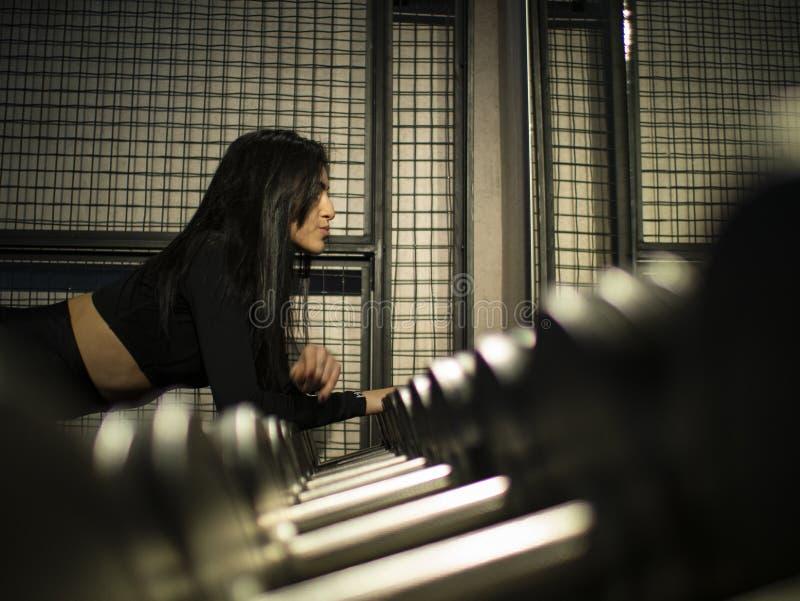 Attraktiver Brunette in einer schwarzen Spitze lehnte sich an einem Regal mit Dummköpfen in der Turnhalle nahe dem Spiegel lizenzfreie stockfotografie