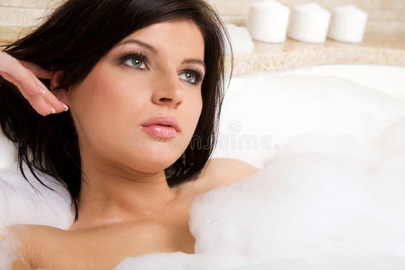 Attraktiver Brunette entspannen sich, ein Bad nehmend. lizenzfreies stockfoto