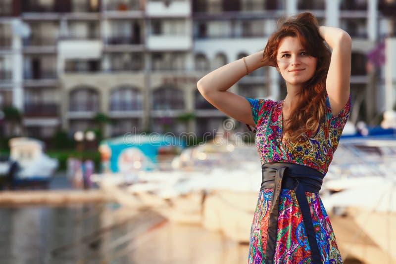 Attraktiver Brunette im langen bunten Kleid, das allein auf dem Strand gegen den Hintergrund von Yachten und von Stadt bei Sonnen stockfoto