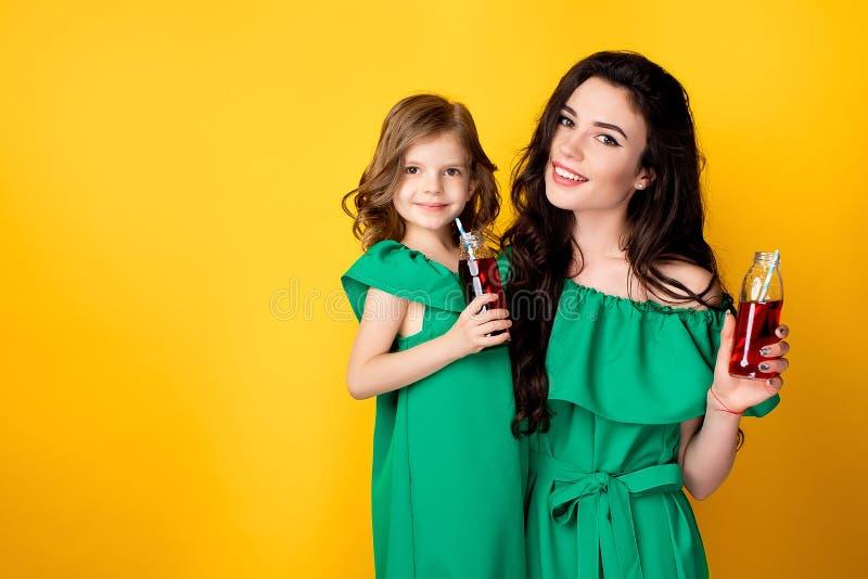 Attraktiver Brunette mit der Tochter, die Rotgetränke hält lizenzfreies stockbild