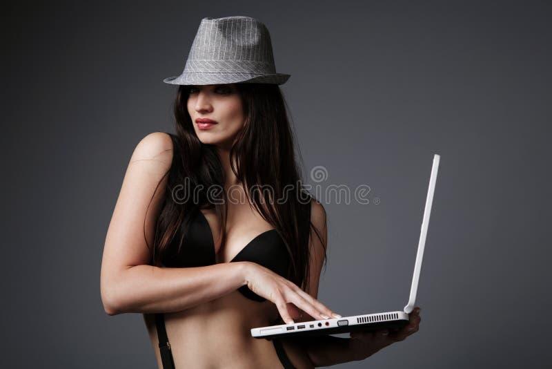 Attraktiver Brunette mit einem Laptop. lizenzfreies stockfoto