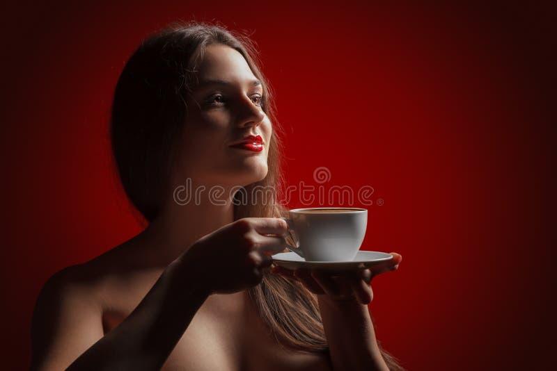 Attraktiver Dame Brunette mit dem Vergnügen, das eine Kaffeetasse in der Hand im Studio hält lizenzfreies stockfoto