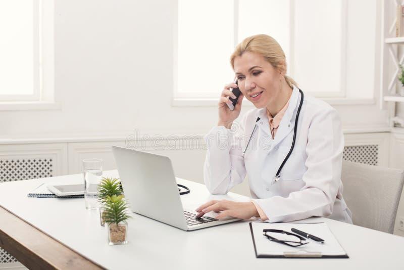 Attraktiver Doktor, der am Telefon mit Patienten spricht lizenzfreies stockfoto