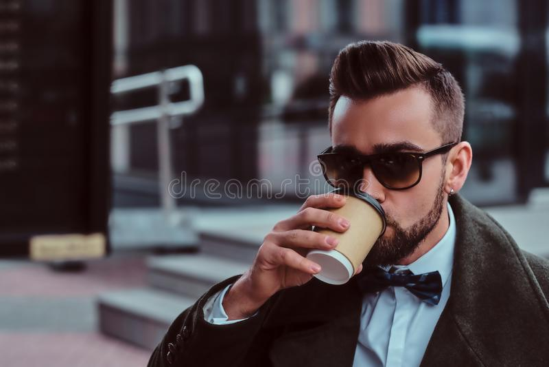 Attraktiver eleganter Mann in der Sonnenbrille trinkt seinen Kaffee beim am coffeeshop draußen sitzen stockfotos