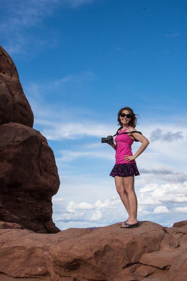 Attraktiver Fotograf der jungen Frau des Sitzes steht auf eine rote Felsformation in Bogen-nationalem PA stockfoto