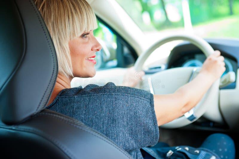 Attraktiver Frauenfahrer in ihrem Auto stockbild